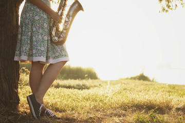 young woman in a dress stands near the tree on the green grass with a wind musical instrument in the hands of dawn