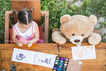 Adorable little girl painting outdoor in a sunny summer day with her teddy bear friend,  seen from above. Outdoor education concept