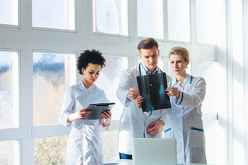 Healthcare, medical: Group of multi-ethnic doctors discussing and looking x-ray in a clinic or hospital.