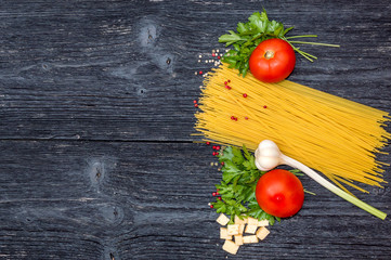 Raw spaghetti with tomatoes, cheese and spices on black wooden b