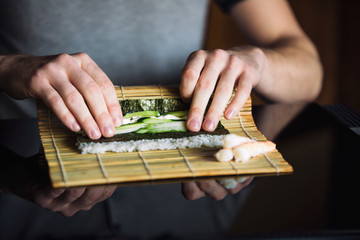 Chef rolling up sushi on a bamboo mat