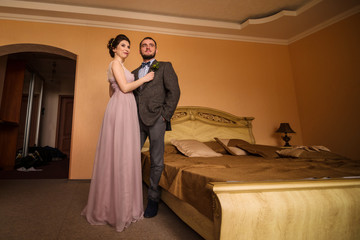 Man and woman standing near the bed at hotel