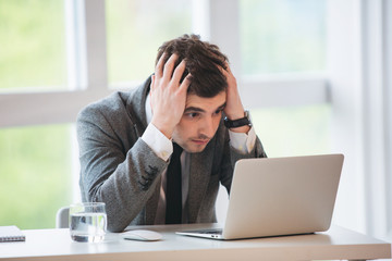 Young businessman gets bad news in office