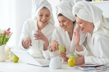 women wearing a white bathrobes with laptop
