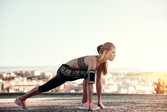 Young sporty female starting to run, standing on the track outdoors. Concept of sport, exercise and healthy lifestyle.