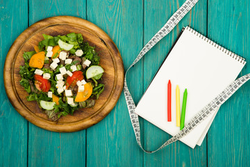 Diet plan - salad of fresh vegetables, tape measure and blank no