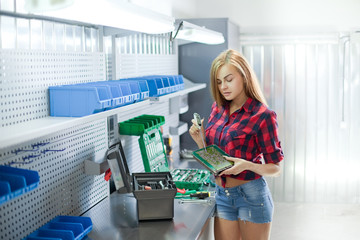 Young brunette sexy woman in checked shirt and jeans in a garage work with electronic plate. Auto diagnostic service