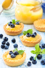 Delicious homemade lemon curd tartlets decorated with fresh blueberries and mint