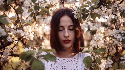 Portrait of pretty young brunette posing in flowering trees