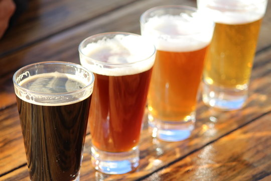 A selection of four craft beers during a tasting session on a wooden table