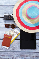Passport and striped beach hat. Tablet and vintage camera. Accessories of modern tourist. Have fun on summer journey.