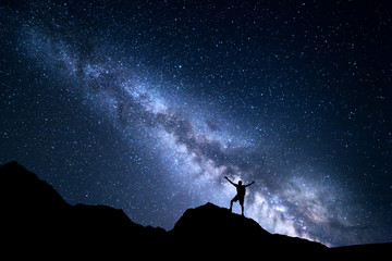 Landscape with Milky Way and silhouette of a happy man