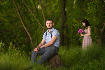 Man sits on the stump and woman stands far away back of him