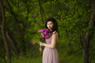 woman holds bouquet of peonies