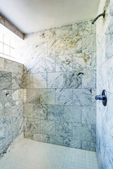 Bathroom interior. Shower cabin with marble tile and small window.