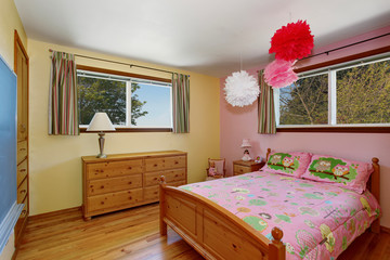 Adorable girls bedroom interior with hardwood floor and pink wall.