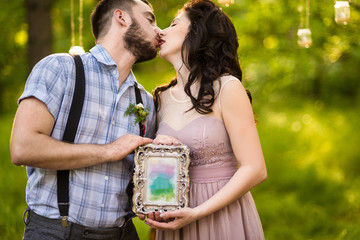Fashion couple in the wood. Kiss. Holds photo frame