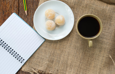 Coffee and sweetmeat.with notebook on Sackcloth brown.