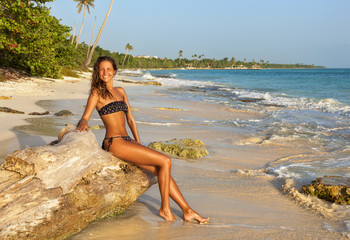 Outdoor photo of beautiful young woman in bikini relaxing on tropical coastline beach. The Caribbean coast of  Dominican Republic.
