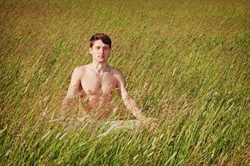 Man sits in grass in lotus pose
