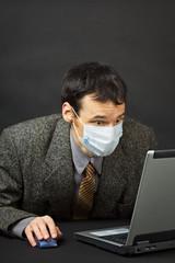Surprised businessman in medical mask works in Internet