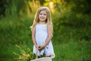 cute little girl with basket of flowers in the park