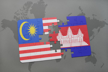 puzzle with the national flag of malaysia and cambodia on a world map background.