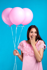Portrait of surprised girl holding balloons