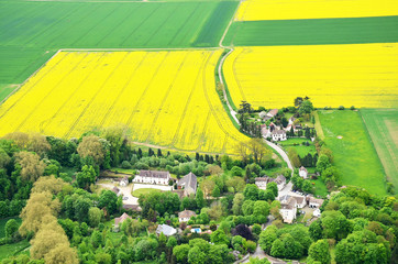 Blooming rapeseed field around the French countryside from the heights.