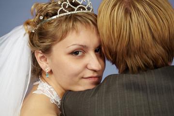 Happy bride on shoulder groom