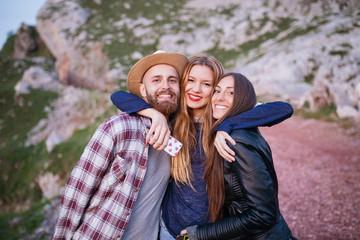 Three friends having fun in a mountain.