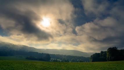 Fotoväggar - Schnell ziehende Wolken lassen die Sonnenstrahlen effektvoll aufs Land fallen