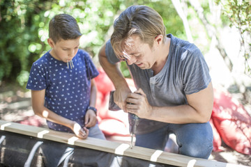Father and son building a sandpit in garden together