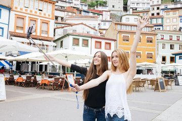 Two girls taking a selfie and having fun in a village.