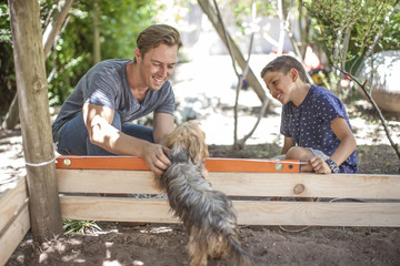 Father and son with dog in garden