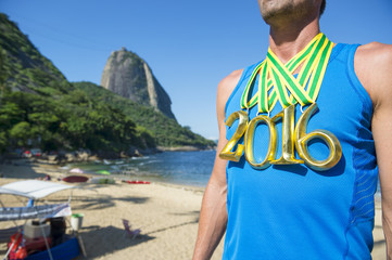 First place 2016 athlete wearing gold medals standing on the beach in front of Sugarloaf Mountain in Rio de Janeiro, Brazil