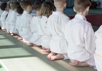 Group of children in kimono sitting on tatami on martial arts training seminar. Selective focus