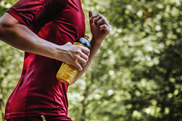 closeup of a young runner with water bottle in hand running through summer Park