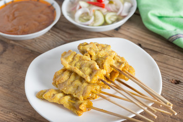 Grilled pork satay with peanut sauce and sour sauce.