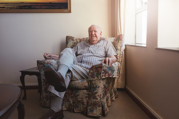 Relaxed elderly man sitting on a arm chair