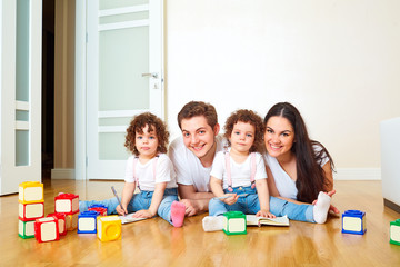 Portrait of a happy family on the floor, playing with cubes. Mot