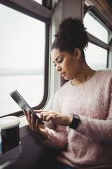 Woman using digital tablet in train