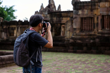 Smart man with backpack taking a photo at old stone castle (Prasat Hin Muang Tum) in Phanom Rung Historical Park,public place in Thailand.