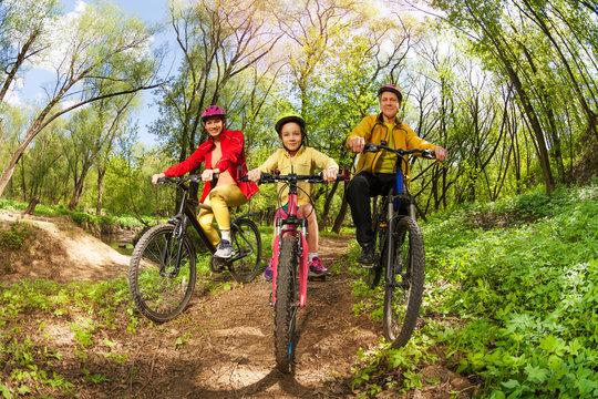 Happy family mountain biking on forest trail