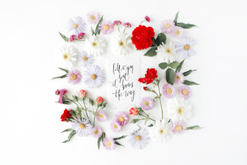 """inspirational quote """"follow your soul it knows the way"""" written in calligraphy style on paper with pink, red roses, chamomiles and leaves isolated on white background. Flat lay, top view"""