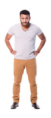 Serious cutout latino man with beard holding hands on his waist. Full length portrait. Isolated on white background.