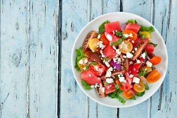 Watermelon and mixed tomato salad with feta cheese, above view on rustic blue wood