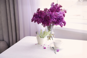 Lilac and may-lily bouquets on white table