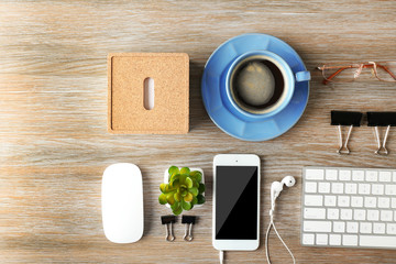 Keyboard, phone and cup of coffee on a wooden desk background, top view