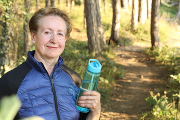 Portrait of happy senior woman hiking in forest